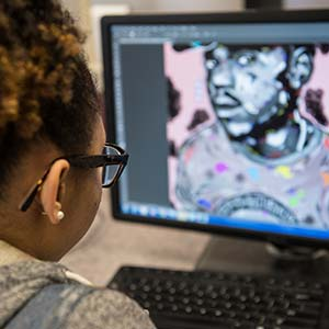 Student editing graphic art on computer